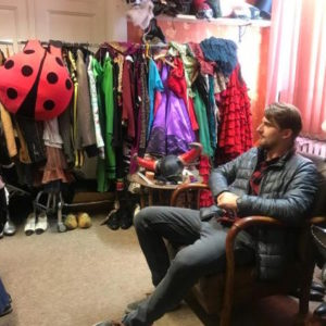A guy on his stag party sitting in a costume rental studio in Poland waiting to be served