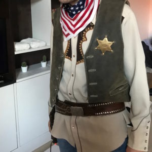 Man from Texas in a Sheriff costume with shirt, vest, star, american scarf and a holster on his stag party