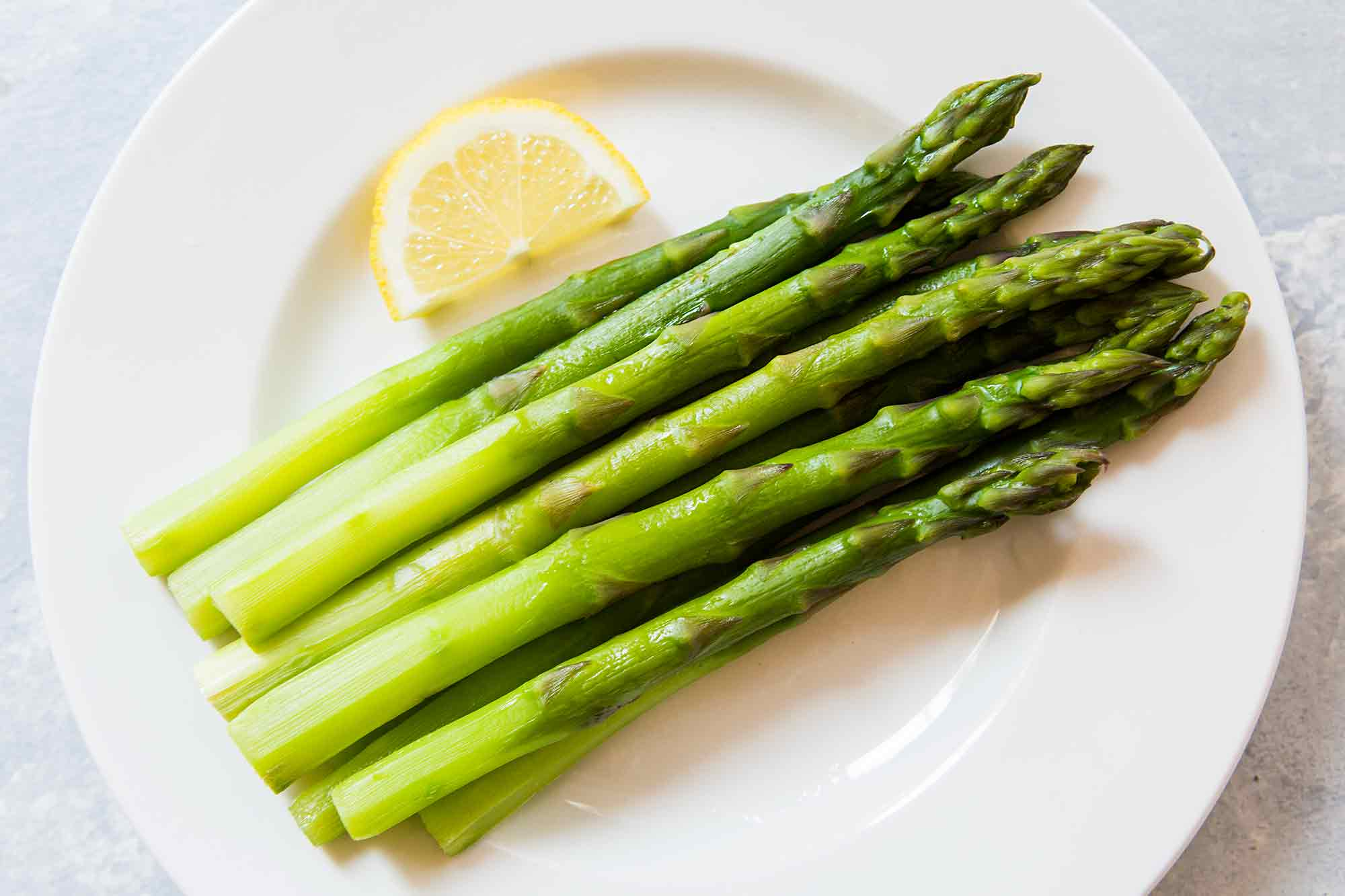 Cooked asparagus on a plate with lemon on side