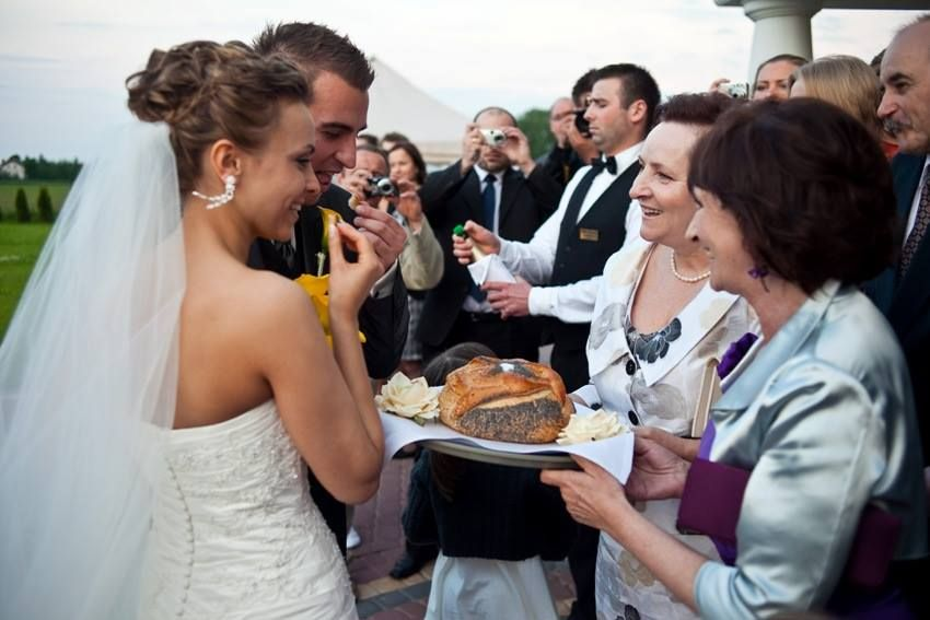 A couple eating bread and salt durring wedding ceremony