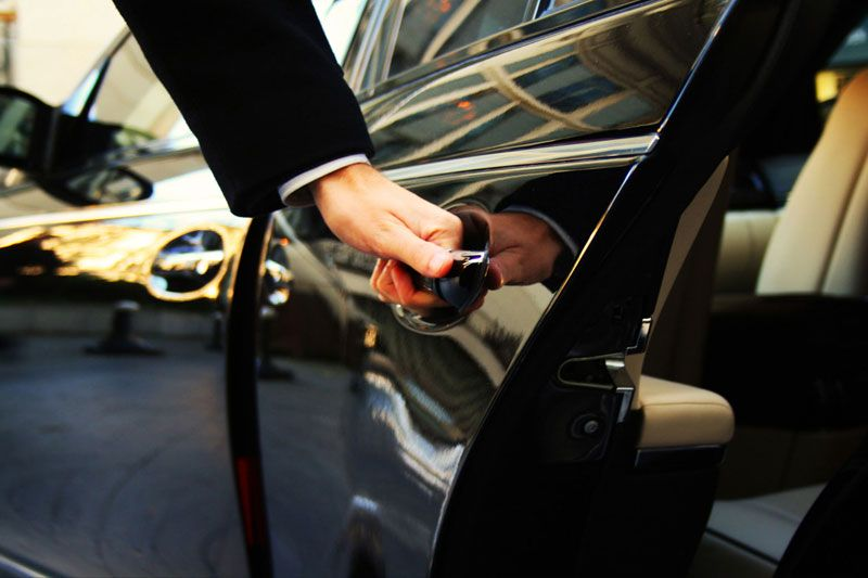 A man opening VIP car door for the passenger